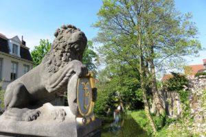 Statut de lion et blason au bord des canaux à Bruges