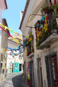 Rue et maisons colorées avec guirlandes fenêtres quartier du château Lisbonne.
