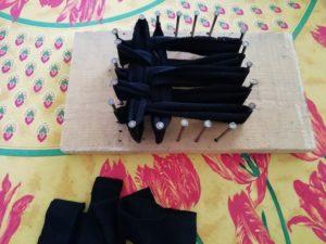 Réalisation d'un tawashi avec des chaussettes sur une planche de bois