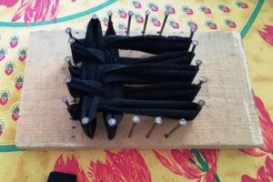 Eponge tawashi en cours de réalisation sur planche de bois avec clous
