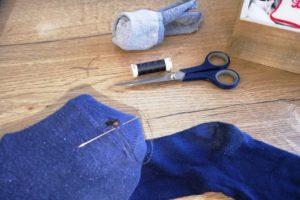 En train de reprise une chaussette avec fil et paire de ciseaux.