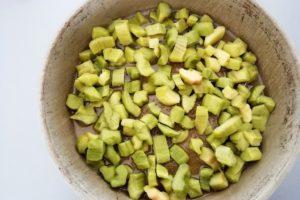Préparation gâteau à la rhubarbe, beurre et sucre roux recouverts de rhubarbe.