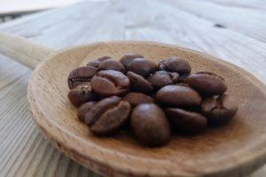 Grains de café dans une cuillère en bois.