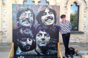 Jef Aérosol posant à côté de son oeuvre des Beatles au château d'Hardelot