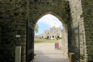 Vue sur le château d'Hardelot, de loin, sous un porche