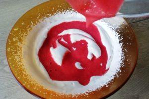 Coulis de fraise en train d'être incorporé dans la crème fouettée